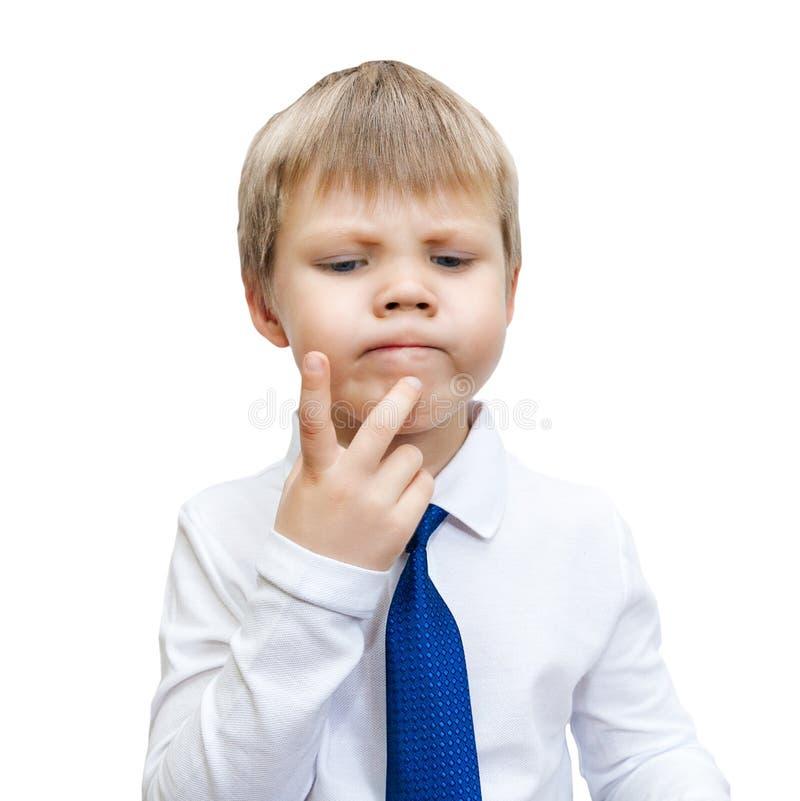 Een kleine jongen in een wit overhemd en een blauwe band denkt royalty-vrije stock foto's