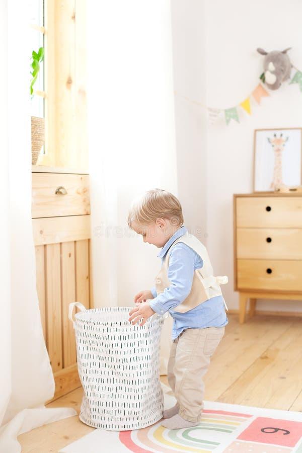Een kleine jongen zet speelgoed in een Skandinavische mand voor een ruimte van kinderen De ruimte van het milieuvriendelijke deco royalty-vrije stock fotografie
