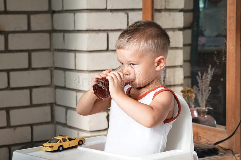 Een kleine jongen zit bij een lijst aangaande de veranda en drinkt compote stock afbeeldingen