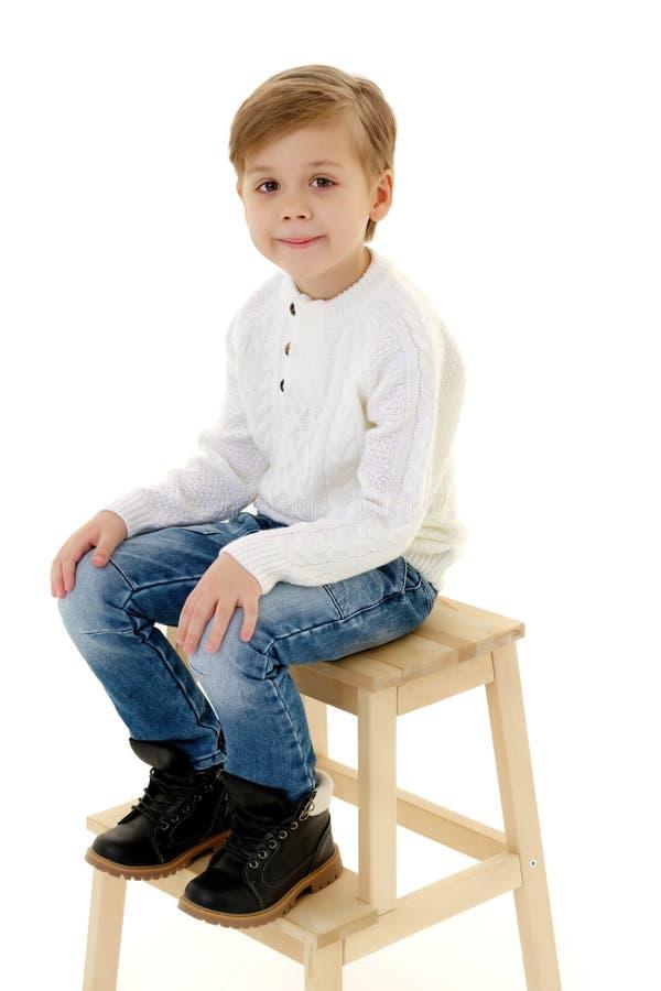 Een kleine jongen zit op een stoel royalty-vrije stock fotografie