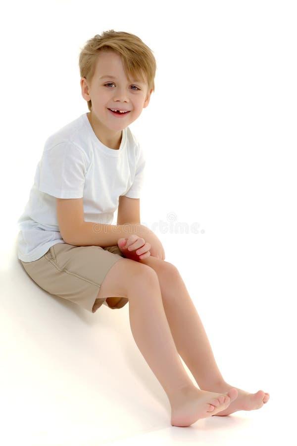 Een kleine jongen in een zuivere witte t-shirt lacht emoties royalty-vrije stock foto