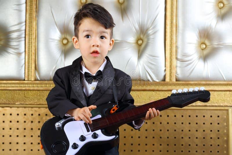 Een kleine jongen in zwarte smoking bevindt zich met gitaar royalty-vrije stock foto