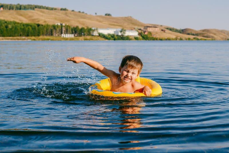 Een kleine jongen zwemt in de reddingsboei op het meer royalty-vrije stock afbeelding