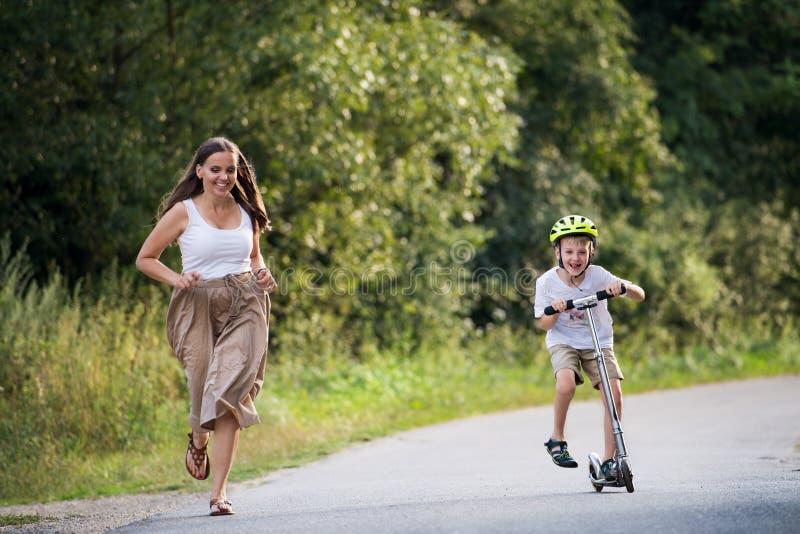 Een kleine jongens berijdende autoped en een moeder die op een weg in park op een de zomerdag lopen stock foto's