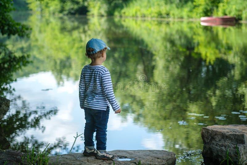 een kleine jongenstribunes zorgvuldig op de Bank van een mooie rivier royalty-vrije stock foto's