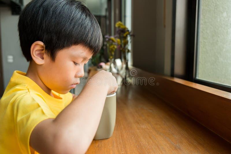 Een kleine jongenszitting bij de houten lijst door het venster thuis om een kop van hete chocolade te drinken hij houdt de kop in stock foto's