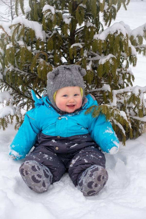Een kleine jongenszitting in de sneeuw onder de boom in de winter royalty-vrije stock afbeeldingen
