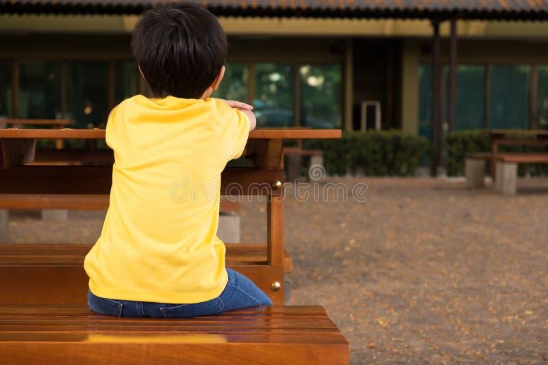Een kleine jongenszitting op de houten lijst met eenzaam gevoel op school hij die op zijn ouders na school wachten stock afbeelding
