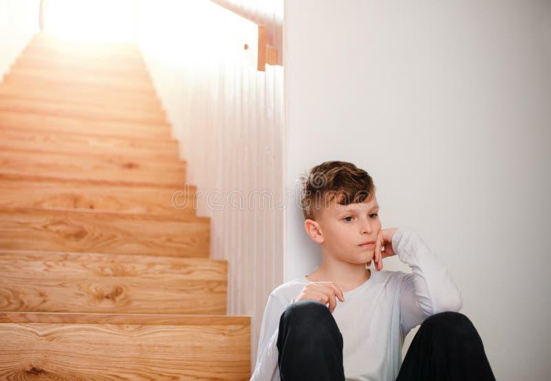 Een kleine jongenszitting op de vloer door de treden De ruimte van het exemplaar stock afbeelding