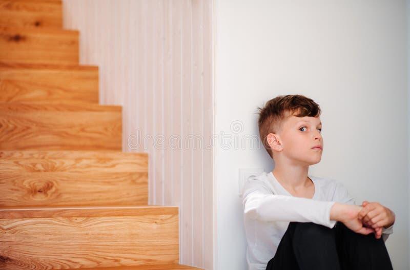 Een kleine jongenszitting op de vloer door de treden De ruimte van het exemplaar royalty-vrije stock afbeelding