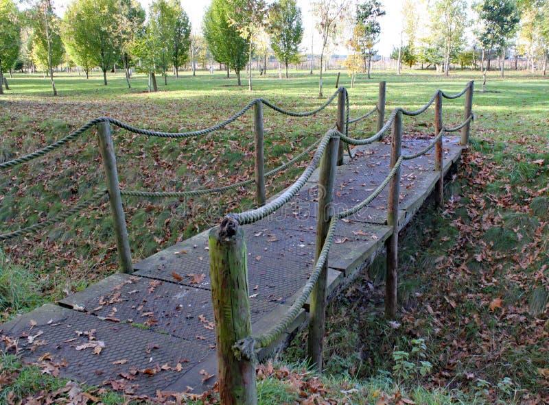 Een kleine kabelbrug kruist een sloot bij Arley-Arboretum in de Binnenlanden in Engeland stock fotografie