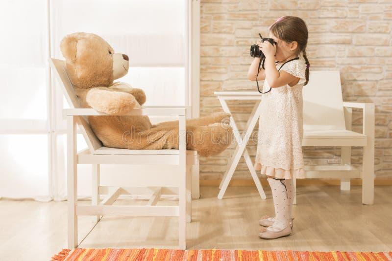 Een kleine kindfotograaf neemt een foto aan haar teddybeer stock fotografie