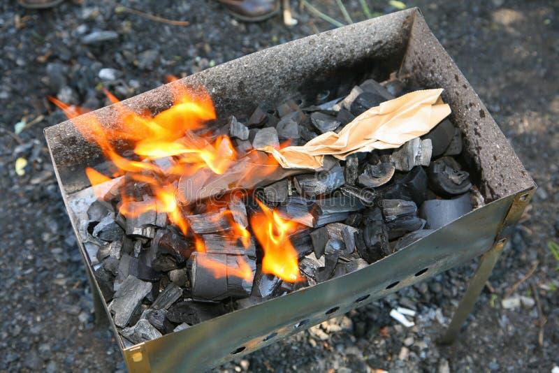Een kleine koperslager met het branden van steenkolen stock foto's