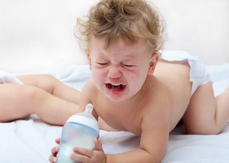 Een kleine krullende jongen bevindt zich op alle fours, die een fles houden stock foto