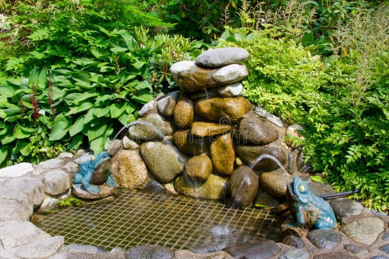 Een kleine kunstmatige waterfontein met rotsen en kunstmatige kikkers dichtbij het Capilano-Hangbruggebied in Vancouver, Canada stock foto