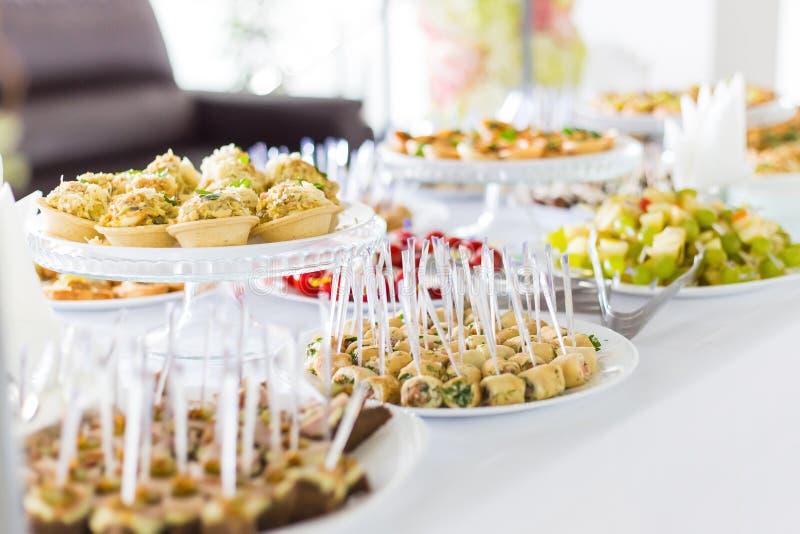 Een kleine lijst met een heerlijk buffet van canapes, kaviaar, sandwiches stock foto