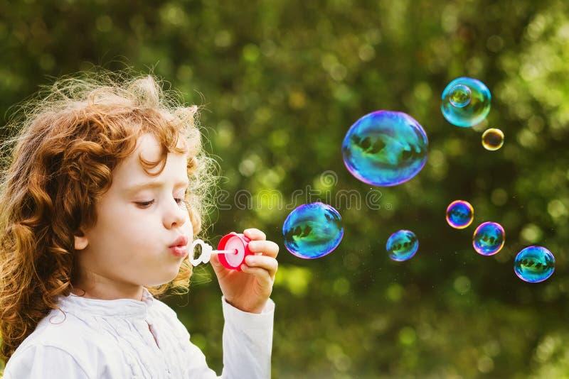 Een kleine meisjes blazende zeepbels, close-upportret mooi c royalty-vrije stock afbeelding