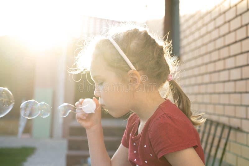 Een kleine meisjes blazende zeepbels in de zomerpark royalty-vrije stock afbeeldingen