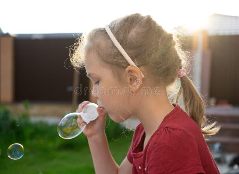 Een kleine meisjes blazende zeepbels in de zomerpark stock foto