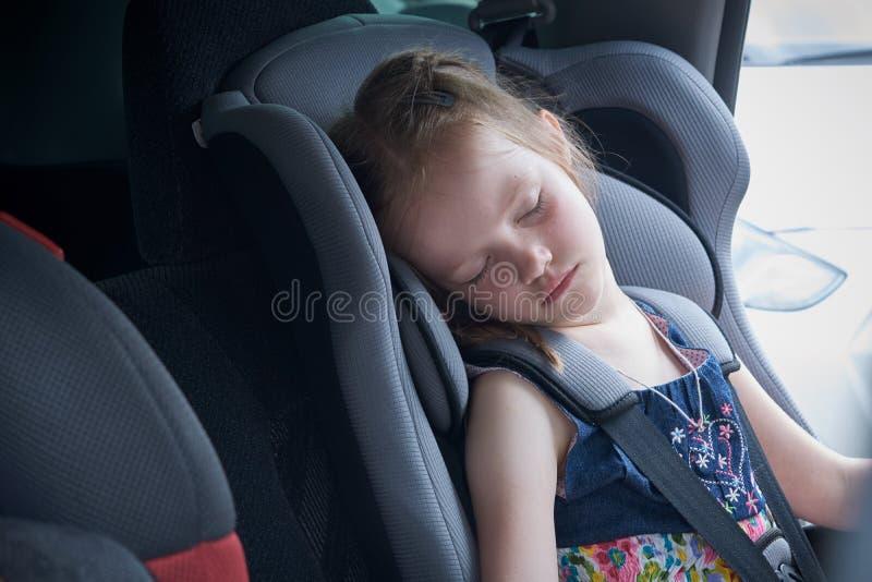 Een kleine meisjesslaap in een comfortabele autozetel voor kinderen royalty-vrije stock afbeelding