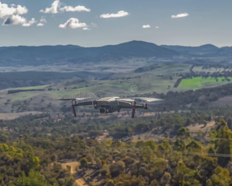 Een kleine moderne onbemande luchtvoertuighommel die tijdens de vlucht telegraafdraden, landschapsmeningen en het landschap die v stock foto