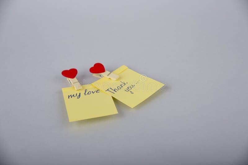 Een kleine nota Leeg document op de koelkastdeur Notadocument met hart Wasknijper met een hart Gele sticker royalty-vrije stock afbeelding
