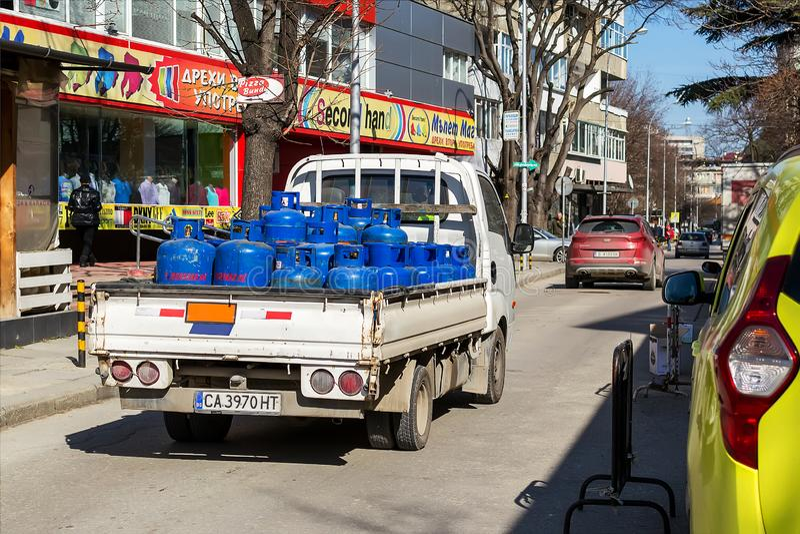 Een kleine open lichaamsvrachtwagen draagt blauwe cilinders met samengeperst gas aan klanten Stadslevering van gasflessen Het ech stock foto's