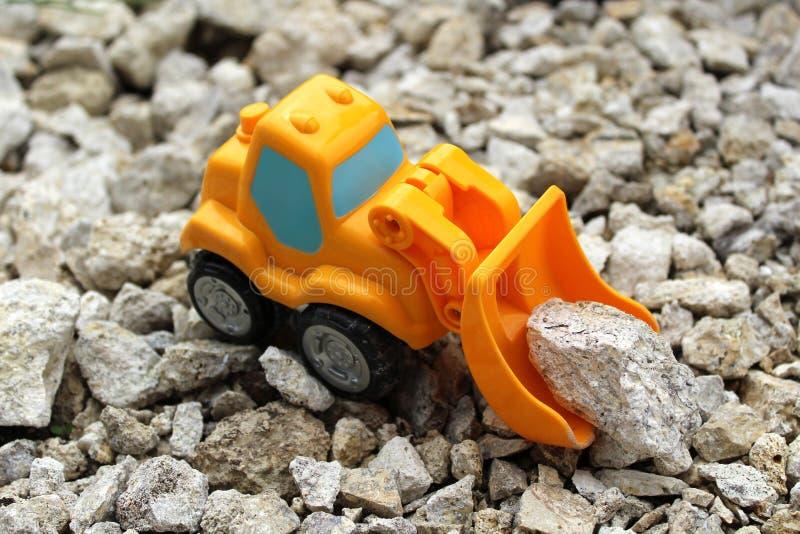 Een kleine oranje stuk speelgoed graver neemt grijze stenen op stock fotografie