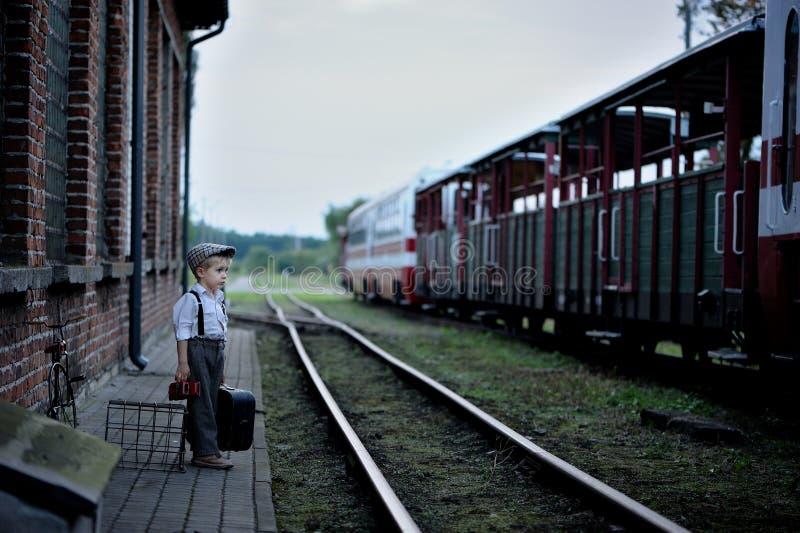Een kleine, peinzende jongen die in retro stijl, het wachten dragen stock afbeeldingen