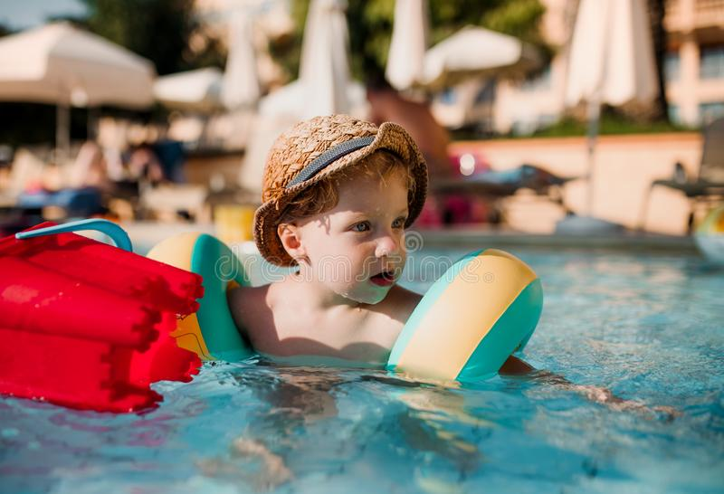 Een kleine peuterjongen met armband die in water op de zomervakantie zwemmen stock afbeeldingen
