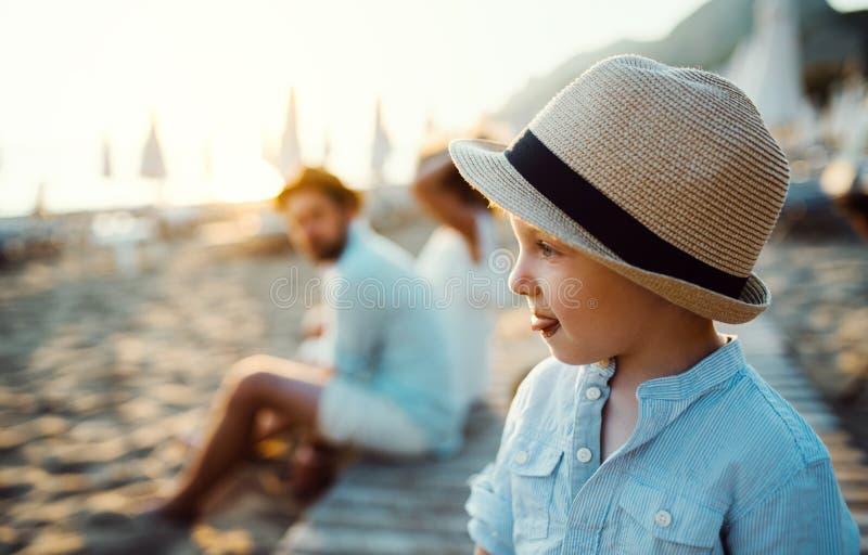 Een kleine peuterjongen met een hoed op strand op de zomervakantie De ruimte van het exemplaar stock foto's