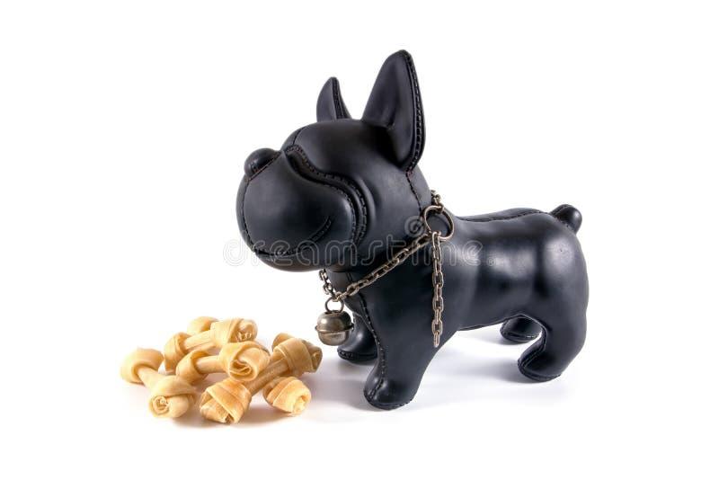 Een kleine plastic die stuk speelgoed hond met ongelooide huidbeenderen op witte bac worden geïsoleerd stock foto's