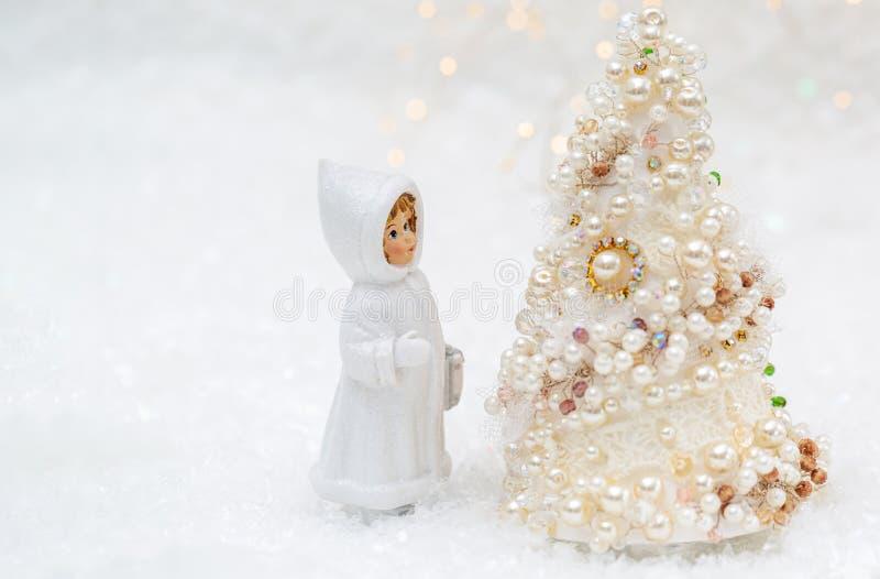 Een kleine pop in de winterkleren bekijkt de Nieuwjaarboom Kerstboom met parels en parels mooie bokehachtergrond stock afbeelding