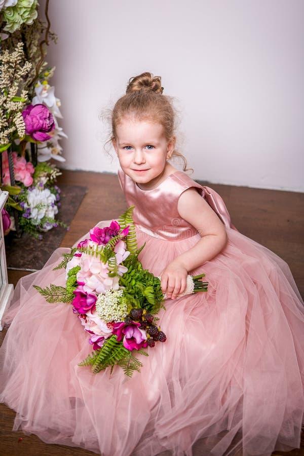 Een kleine prinses in een mooie roze kleding zit op de vloer dichtbij bloemtribunes en de lantaarns, houdt een boeket van pioenen stock afbeeldingen