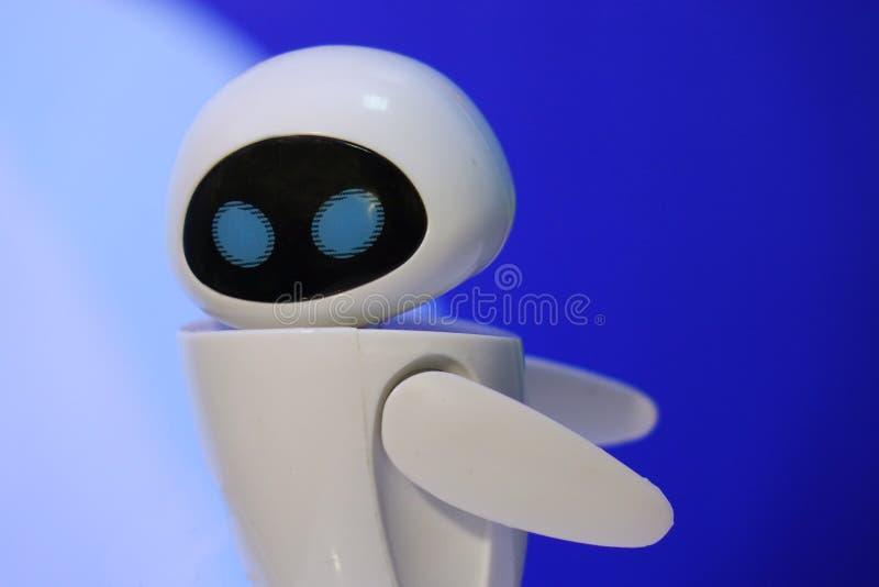 Een kleine robot met een humanoidlichaam op een blauwe achtergrond Kunstmatige intelligentie-AI Blauw-witte robot stock afbeeldingen