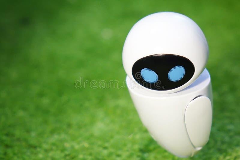 Een kleine robot met een humanoidlichaam op een geïsoleerde groene achtergrond Kunstmatige intelligentie-AI royalty-vrije stock afbeelding