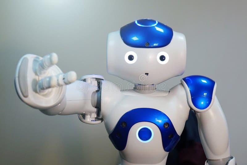 Een kleine robot met een menselijk gezicht en een humanoidlichaam Kunstmatige intelligentie - AI Blauw-en-witte robot stock afbeelding