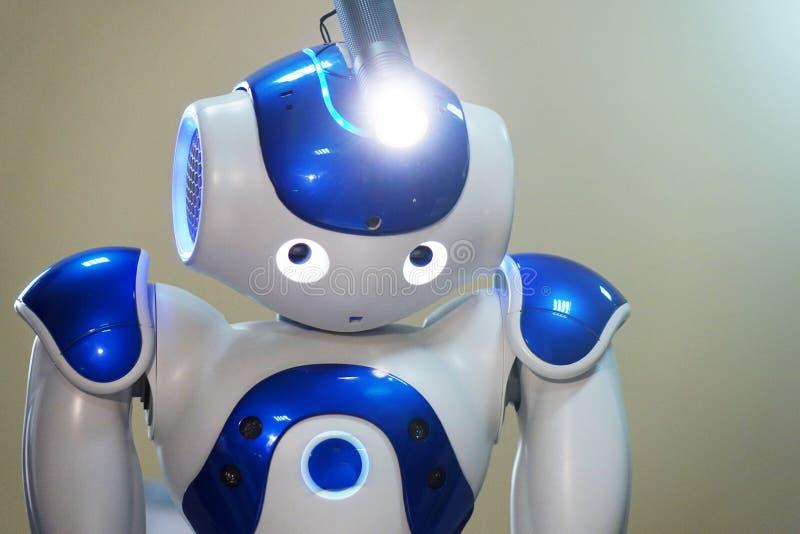 Een kleine robot met een menselijk gezicht en een humanoidlichaam Kunstmatige intelligentie - AI Blauw-en-witte robot royalty-vrije stock afbeelding