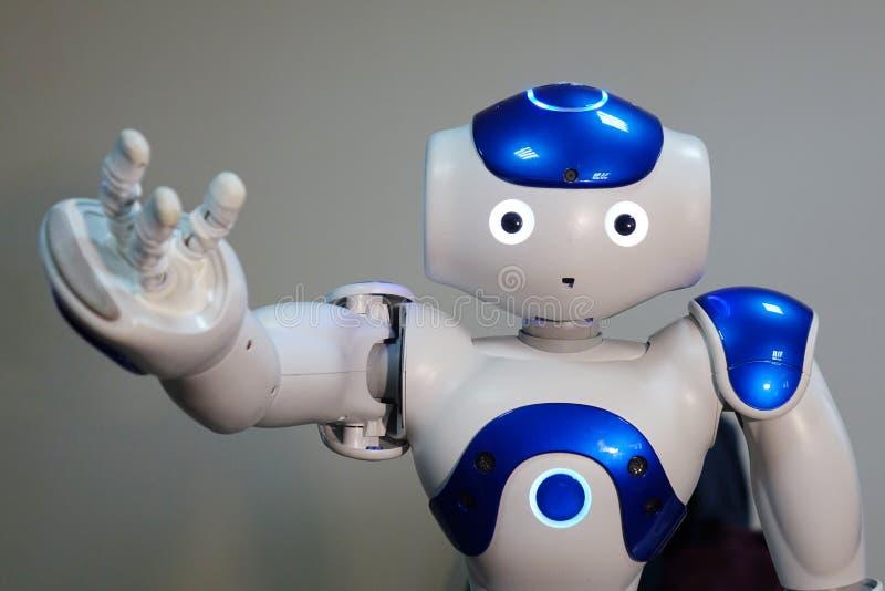 Een kleine robot met een menselijk gezicht en een humanoidlichaam Kunstmatige intelligentie - AI Blauw-en-witte robot stock foto