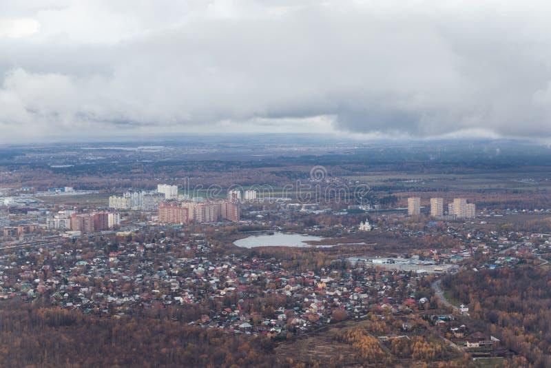 Een kleine stad van de hoogte vliegtuigen High-rise gebouwen dichtbij het meer Mening van de aarde van een vliegtuig royalty-vrije stock afbeelding
