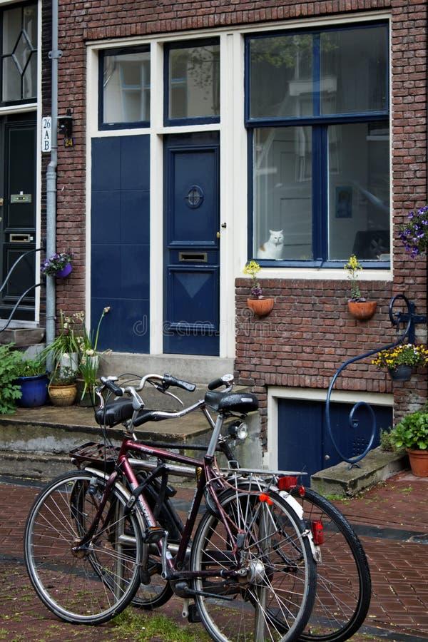 Een kleine straat in Amsterdam en fietsen dichtbij het huis stock afbeeldingen