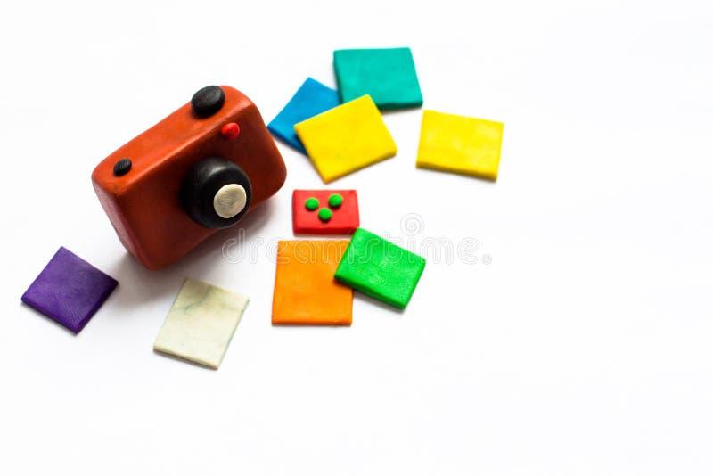 Een kleine uitstekende camera van bruine kleur wordt gemaakt van plasticine Naast de camera is een paar foto's van heldere en kle royalty-vrije stock afbeeldingen
