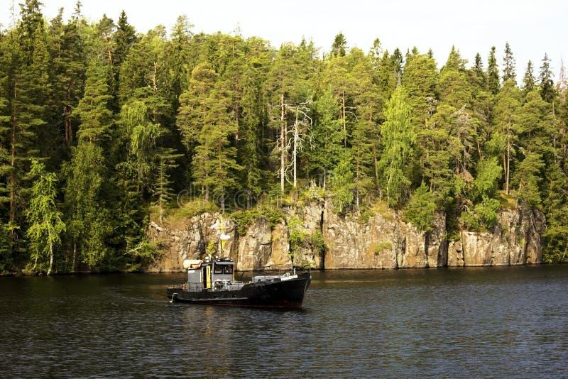 Een kleine vissersboot tegen de rotsachtige beboste kust van het Eiland Valaam royalty-vrije stock fotografie