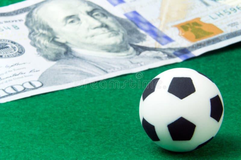 Een kleine voetbalbal op een groene achtergrond naast een honderd-dollar rekening Conceptengeld en sporten, die op voetbal wedden royalty-vrije stock afbeelding