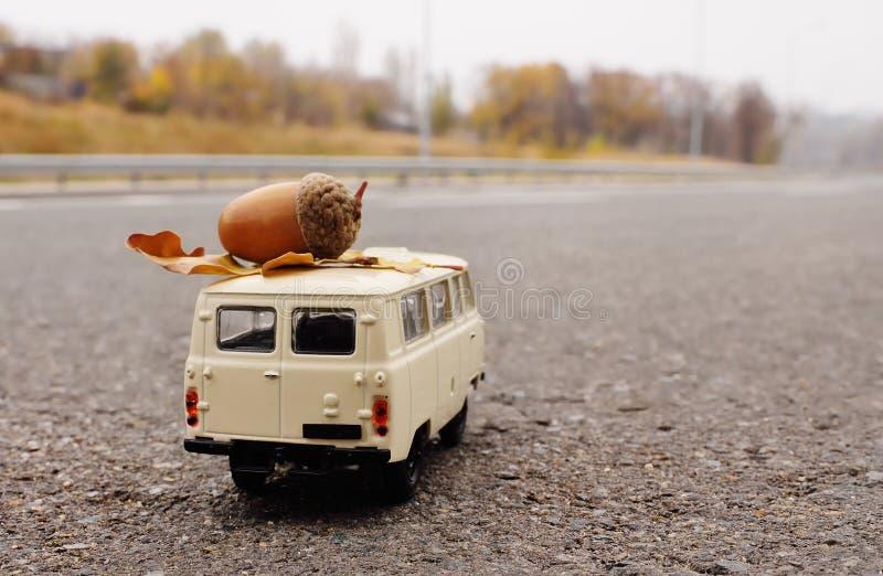 Een kleine witte stuk speelgoed auto draagt een eikel op het dak tegen de achtergrond van geel de herfstbomen en bos stock afbeeldingen