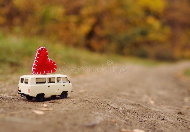 Een kleine witte stuk speelgoed minivan auto wordt gedreven op het dak van een groot rood hart op de achtergrond van de herfst ge stock foto's