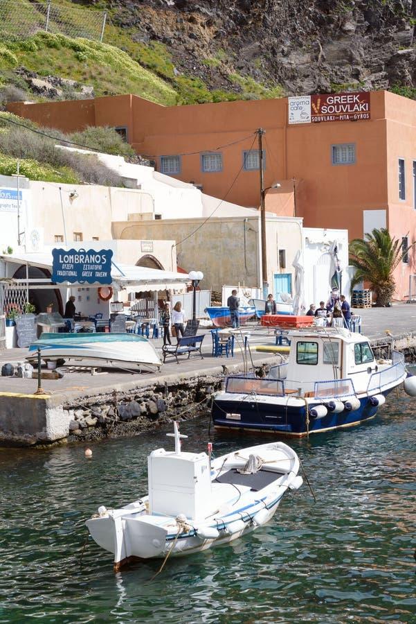 Een kleine witte vissersboot in de oude haven van de Griekse stad van Fira royalty-vrije stock foto