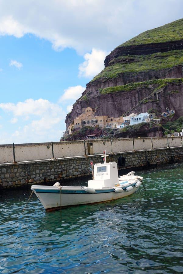 Een kleine witte vissersboot in de oude haven van de Griekse stad van Fira stock foto