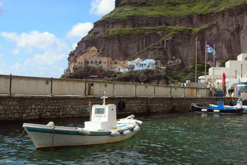 Een kleine witte vissersboot in de oude haven van de Griekse stad van Fira royalty-vrije stock afbeeldingen