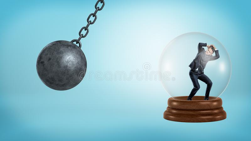 Een kleine zakenman bevindt zich binnen een glasgebied met een slingerende slopende bal bedreigend hem stock afbeelding